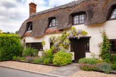 Maison couverte de chaume anglaise traditionnelle avec la décoration de fleur dans Sou photo stock