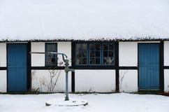 Maison couverte de chaume avec les fenêtres bleues et les portes, tout snowclad Images stock
