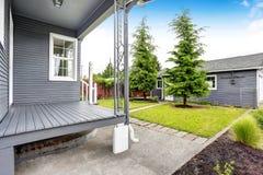 Maison d'arrière-cour avec l'équilibre de voie de garage, porche en bois de plancher, passage couvert concret Image stock