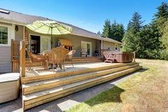 Maison d'arrière-cour extérieure avec le secteur de patio et le baquet chaud sur la plate-forme de débrayage Photo stock