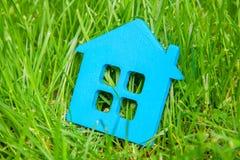 Maison d'Eco en nature Symbole de bleu de maison sur l'herbe verte en été Photographie stock