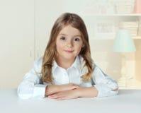 Maison d'intérieur de portrait de fille d'enfant Femelle d'élève à la table lifestyle Photos libres de droits