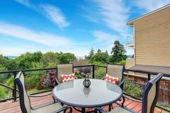 Maison de balcon extérieure avec les balustrades en verre, l'ensemble de table et la vue parfaite Image libre de droits