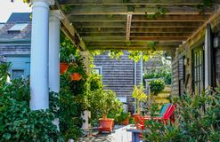 Maison de bardeau avec le porche louche avec le toit de pergola avec des vignes et d'autres plantes s'élevant dans la profusion e images stock
