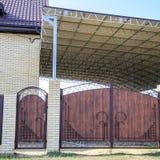 Maison de brique avec une barrière et des portes Une grande tente avec un cadre en acier Vue d'une nouvelle barrière bâtie et d'u photographie stock