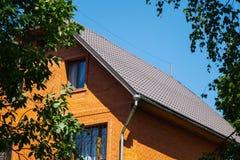 Maison de brique rouge avec le drainage et les grilles décoratives de fenêtre photos stock