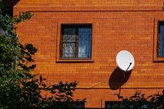 Maison de brique rouge avec les grilles décoratives de fenêtre et l'antenne parabolique blanche photos libres de droits