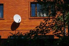 Maison de brique rouge avec les grilles décoratives de fenêtre et l'antenne parabolique blanche photographie stock