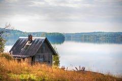 Maison de campagne en bois sur le rivage de lac Image libre de droits