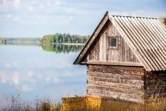Maison de campagne en bois sur le rivage de lac Images stock