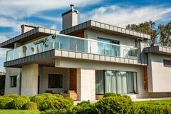 Maison de campagne moderne avec la grande pelouse et une barrière en bois Devant la maison il y a une terrasse couverte avec une  photos libres de droits