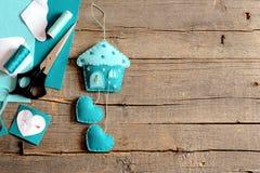 Maison de feutre avec le décor de coeurs, ciseaux, fil, aiguille, modèles de papier sur le vieux fond en bois avec l'espace de co Image stock