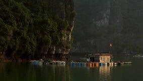 Maison de flottement dans la baie de Halong sur le coucher du soleil banque de vidéos