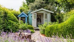 Maison de jardin dans un jardin coloré avec le patio Images stock