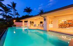 Maison de luxe avec la piscine au coucher du soleil images stock