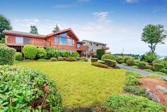 Maison de luxe extérieure avec l'équilibre en bois de panneau, le garage et le jardin soigné autour images libres de droits