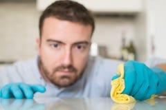 Maison de nettoyage d'homme avec les gants protecteurs Image stock