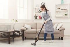 Maison de nettoyage de jeune femme avec l'aspirateur image libre de droits