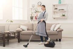 Maison de nettoyage de jeune femme avec l'aspirateur photos stock
