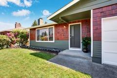 Maison de niveau de l'Américain un extérieure avec le garage et le jardin soigné photos stock