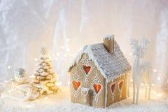 Maison de pain d'épice, arbres de Noël et un chiffre d'un cerf commun sur un fond lumineux Effet de Bokeh Photos libres de droits