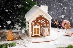Maison de pain d'épice faite maison, neige en baisse et décorations de fête de Noël Photographie stock