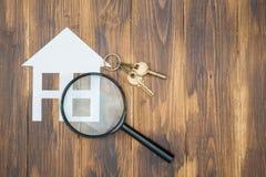 Maison de papier et clé avec la loupe, recherche de logement Photos libres de droits