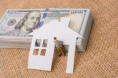 Maison de papier et une figurine d'homme près de billet de banque de dollar US Photo stock