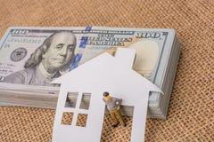 Maison de papier et une figurine d'homme près de billet de banque de dollar US Photographie stock libre de droits
