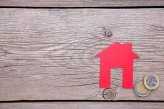 Maison de papier rouge avec le toit rouge, avec des pièces de monnaie sur le fond gris photos libres de droits