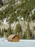 Maison de rondin en hiver devant une montagne Images libres de droits
