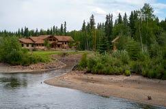 Maison de rondin le long de la rivière Image stock
