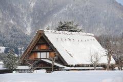 Maison de toit couvert de chaume couverte dans la neige Photos stock