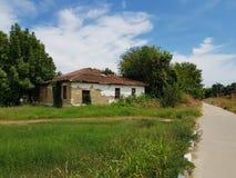 Maison de village à côté de la route entre les arbres, l'herbe et le ciel image libre de droits