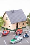 Maison de ville, personnes miniatures et voitures sur une rue passante Photos libres de droits