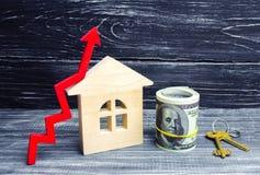 Maison, dollars et clés en bois avec une flèche rouge  concept de forte demande pour les immobiliers augmentez le rendement énerg Image stock