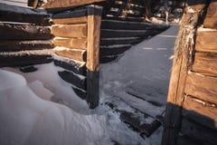 Maison en bois abandonnée dans les montagnes d'hiver au lever de soleil Photos libres de droits