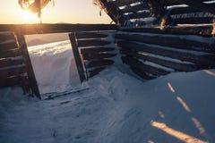 Maison en bois abandonnée dans les montagnes d'hiver au lever de soleil Photo libre de droits