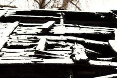 Maison en bois abandonnée neigeuse du feu de burn-out de photo noire et blanche photographie stock