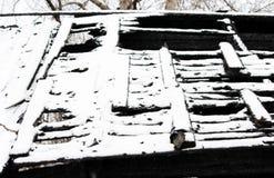 Maison en bois abandonnée neigeuse du feu de burn-out de photo noire et blanche photos stock