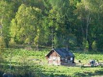 Maison en bois avec de la fumée d'un tuyau dans les bois du lac Baïkal (Russie) photos libres de droits
