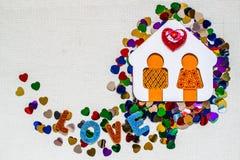 Maison en bois avec le petit homme et les confettis lumineux en forme de coeur Images libres de droits
