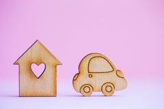 Maison en bois avec le trou sous la forme de coeur avec l'icône en bois de voiture dessus Photo libre de droits