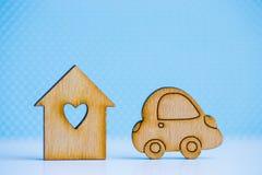 Maison en bois avec le trou sous la forme de coeur avec l'icône en bois de voiture dessus Photo stock