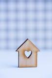 Maison en bois avec le trou sous la forme de coeur sur le backgr à carreaux gris Photographie stock libre de droits