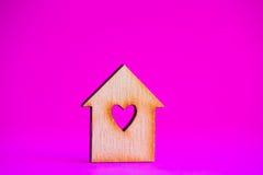 Maison en bois avec le trou sous la forme de coeur sur le fond cramoisi Images stock