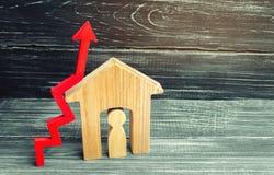 Maison en bois avec un homme à l'intérieur Flèche rouge vers le haut concept de haut De Photographie stock libre de droits