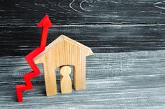 Maison en bois avec un homme à l'intérieur Flèche rouge vers le haut concept de forte demande pour les immobiliers augmentez le r Photographie stock