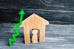 Maison en bois avec un homme à l'intérieur Flèche verte vers le haut concept de forte demande pour les immobiliers augmentez le r Images libres de droits
