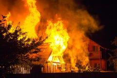 Maison en bois brûlante la nuit Flammes oranges lumineuses et SM dense photo stock